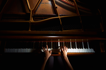 Woman's hands playing on the keyboard of the piano in night closeup Foto de archivo