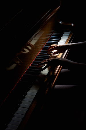 Woman's hands playing on the keyboard of the piano in night closeup Banque d'images