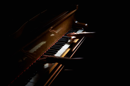 Woman's hands playing on the keyboard of the piano in night closeup 写真素材