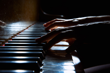 Womans hands playing on the keyboard of the piano in night closeup Reklamní fotografie