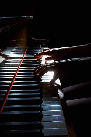 dedo: manos de la mujer tocando en el teclado del piano en primer plano la noche