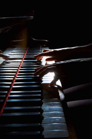 piano closeup: Womans hands playing on the keyboard of the piano in night closeup Stock Photo
