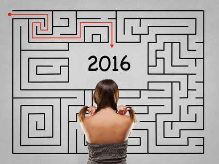 grey hair: Woman pulling hair in front of grey labyrinth with 2016 solution Stock Photo