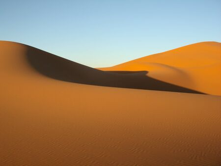 sahara: Sand dunes in the desert with blue sky Stock Photo