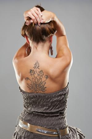 灰色の背景のスタジオ撮影でタトゥー女性の肖像画