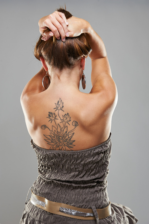 Tattoo woman portrait in studio shoot on grey background Banque d'images