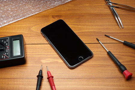 repaired: Repaired smartphone with tools on table in wood