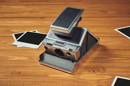 Polaroid camera and film on wood table