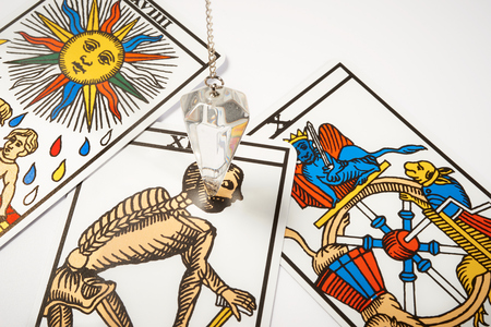 White crystal Pendulum with blur tarot cards
