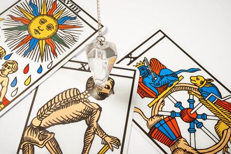 astrologer: White crystal Pendulum with blur tarot cards
