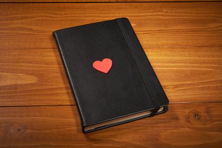 木製のテーブルに赤いハートのバレンタインの日ノート