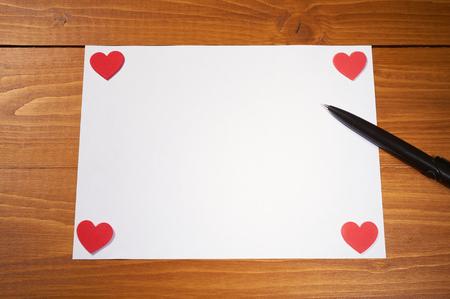 バレンタインデー ホワイト ペーパーでは、木製のテーブルに赤いハート