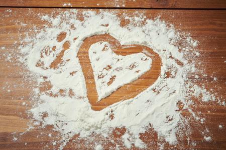 木製のテーブルから小麦粉でバレンタインデー ハート