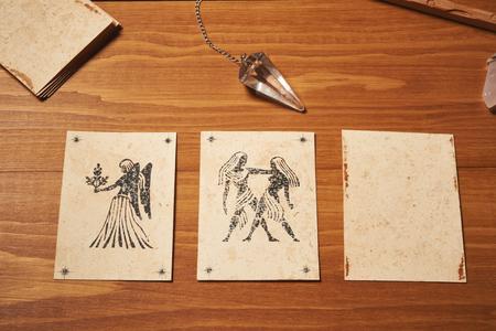 テーブルの上にクリスタル振り子が付いているクレアボヤンスカード