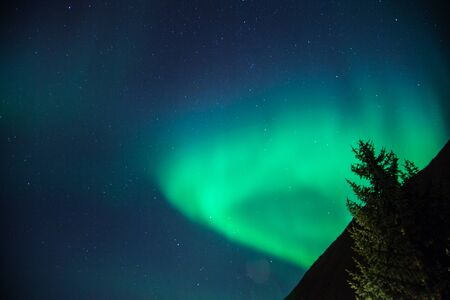 Northern lights arise over a mountain