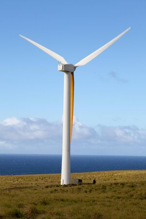Wind generator spins in an open field overlooking Pacific Ocean