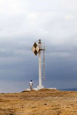 watchman: A lone watchman stands at base of rural lighthouse.