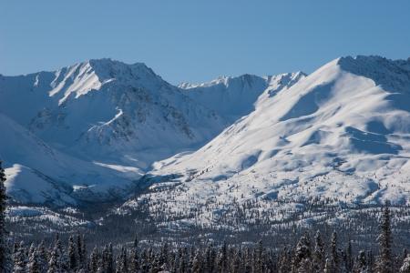 sharply: Winter mountains rise sharply above the landscape of Interior, Alaska Stock Photo