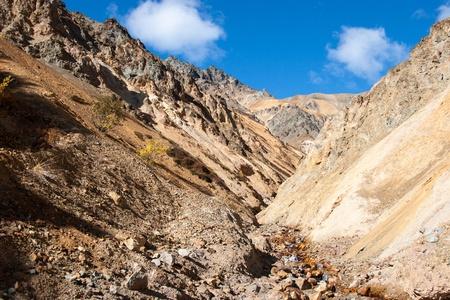 descends: A small creek descends down steep mountain valley