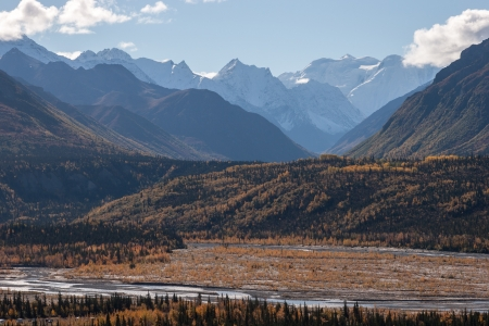 rise above: Rugged snow capped peaks rise above autumn lowlands