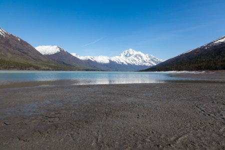 mud and snow: A large blue lake begins to melt on a hot spring day Stock Photo