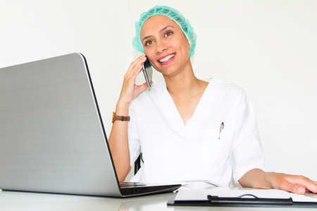 A young woman doctor With a laptop in her office talking on the phone