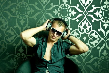 sexy headphones: Cool guy sitting on an armchair Stock Photo