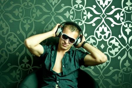 listening to music: Individuo fresco que se sienta en un sill�n