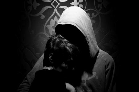 Uomo senza volto in possesso di una ragazza al petto