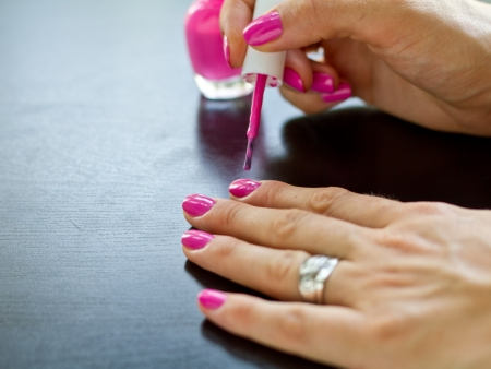 Woman painting her nails in pink
