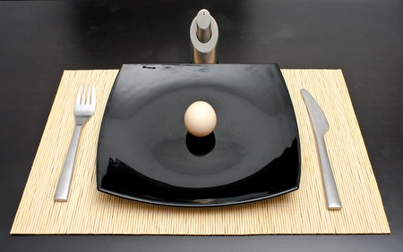 Dinner egg in a black plate photo
