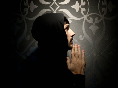 Young caucasian man with hood and beard praying photo