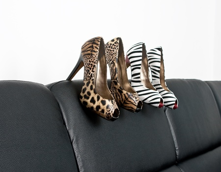 Two pairs of womans shoes on a black sofa photo