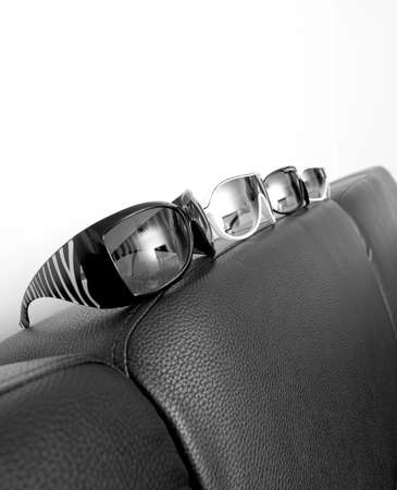 Four pairs of sunglasses on a black sofaback rest photo