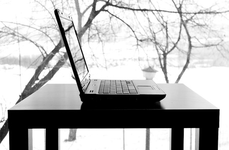 Laptop silhouette on a wooden table photo