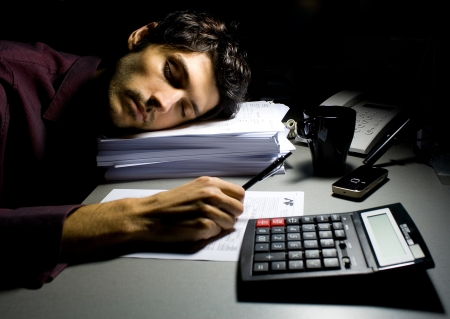 Young business man sleeping on a pile of documents photo