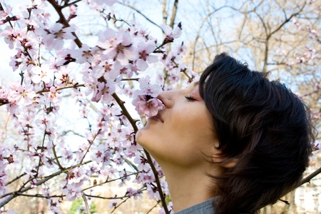 Young girl smelling the blossomming flowers of a tree photo