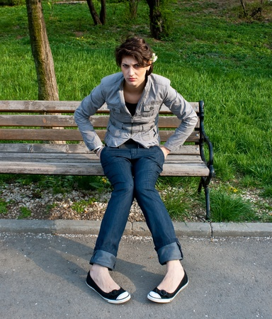 Upset girl sitting on a bench photo