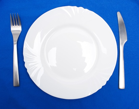 Table arrangement of fork and knife besides a plate photo