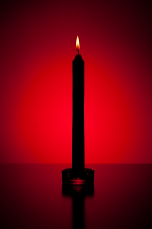 Candle in red lit backgrounded photo
