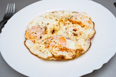 Traditional Indian eggs with curry and hot red pepper photo