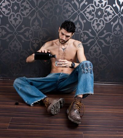 lonely boy: Bearded man on the floor drinking Stock Photo