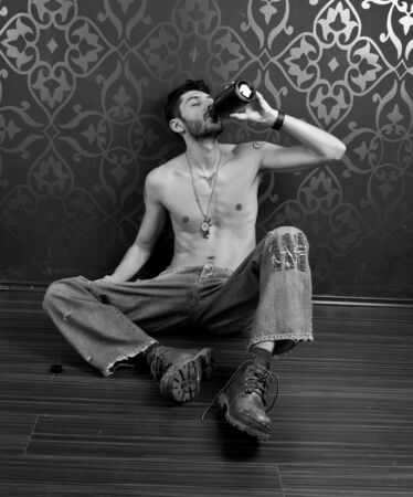 Skinny man on the floor drinking photo
