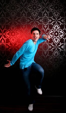 Teenager dancing with red spotlight in the background photo