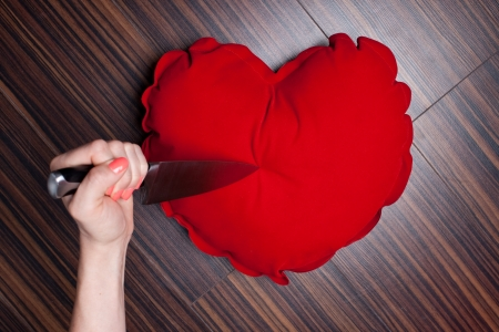 Woman's hand holding a knife to a heart pillow 版權商用圖片