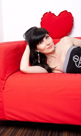 Woman looking at the camera laying on a sofa Stock Photo - 15260303