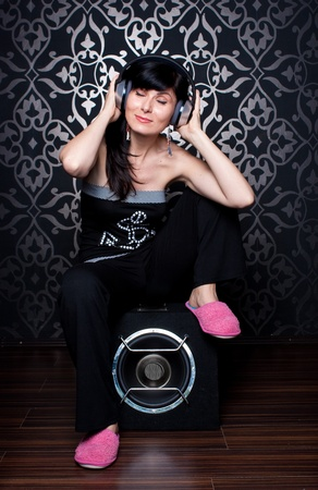 Cool girl sitting on a subwoofer with headphones on photo