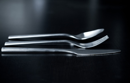 Silverware on black table (shallow DOF, focus on fork) photo