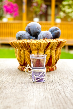 Plums in a whicker basket (focus on the glass) photo