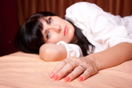 Woman laying in the bed in a man's shirt (focus on hand) photo